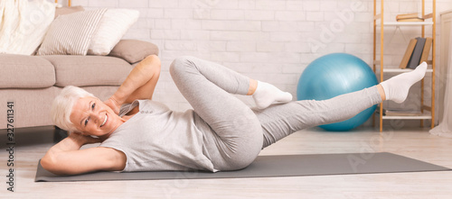 Active senior woman exercising on floor at home, panorama - 327611341