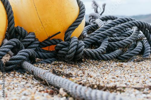Foto Boyas de colores en la playa encima de la arena junto a una cuerda larga