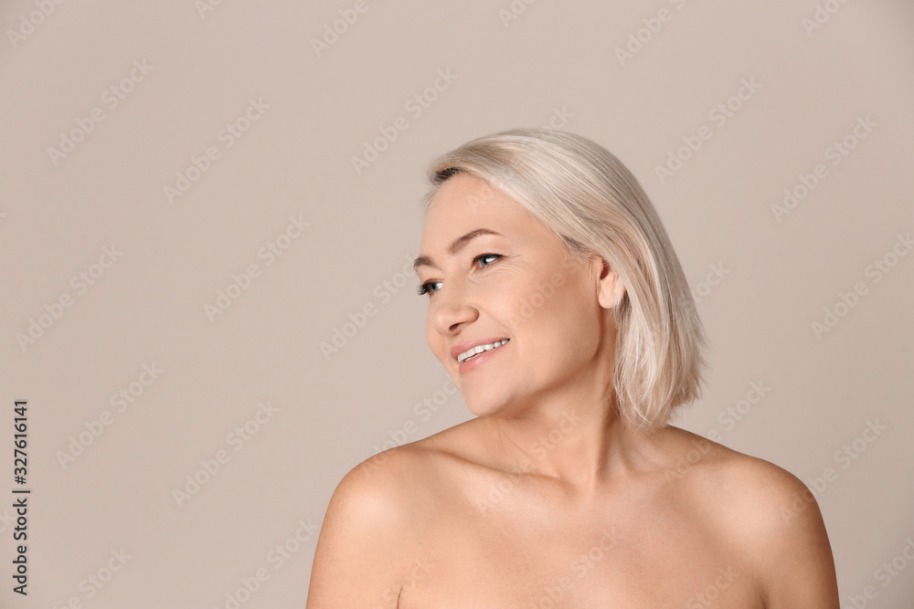Fototapeta Portrait of beautiful mature woman on beige background. Space for text