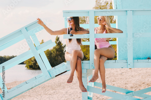 Two carefree women friends drinking cold lemonade and laughing while sitting on lifeguard tower. Girl pointing away, calling someone for party. Happy girls cheering with soft drinks on sunny beach
