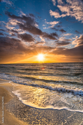 colored sunset with cloud cover over the sunset at the beach - dramatic sunset on the baltic sea #327629545