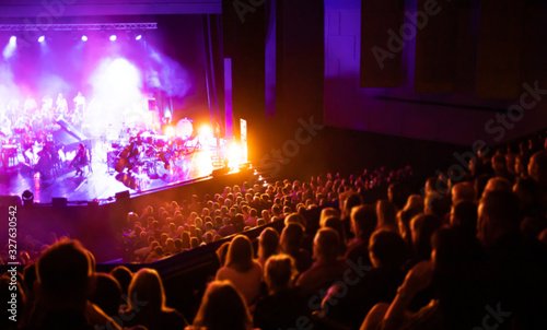 Obraz Lights on stage during concert in hall filled with spectators - fototapety do salonu