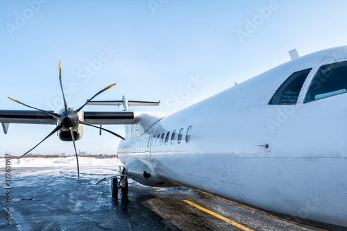 Vászonkép A close-up of the fuselage of a white passenger turboprop airplane on the winter
