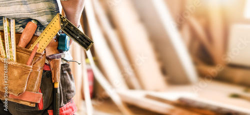 Obraz The carpenter with measuring and work tools in leather belt. Wide banner or panorama concept. - fototapety do salonu
