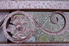 The Forged Fence Element Is Covered In Brown Paint, And The Recent Rain Has Left A Drop Of Water On It. Beautiful Forged Pattern.