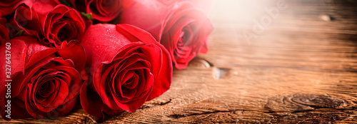 Red roses on vintage old wooden board. Valentines day web wide rose banner