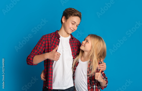 Little brother and sister embracing and showing thumbs up, blue background Fototapet