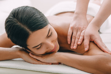 Beautiful woman enjoying massage at the spa.