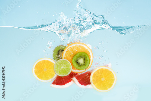 Fototapety, obrazy: Sliced tropical fruits falling into transparent water with splashes on blue background