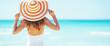 Leinwandbild Motiv Young woman in hat standing on beach. rear view