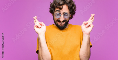 Photographie young crazy cool man smiling and anxiously crossing both fingers, feeling worrie