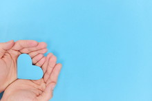 Blue Heart Shape Cutout On Hands In Blue Background. Top View, Kindness And Charity Concept.