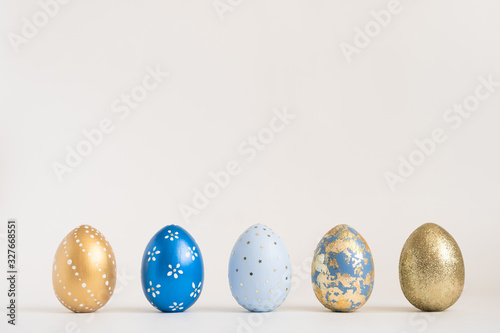 Fototapeta Easter golden decorated eggs stand in a row on blue background. Minimal easter concept. Happy Easter card with copy space for text. Top view, flatlay obraz