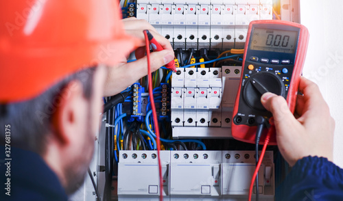 Fotomural Electrician installing electric cable wires of fuse switch box.
