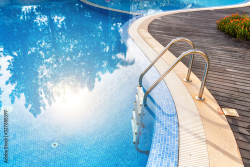 Fototapeta Steps into the pool with handrails in water reflex sun. For tourists. obraz