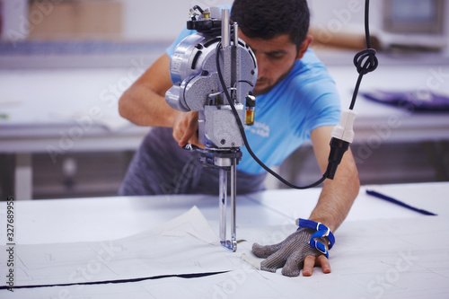 Obraz Young cutter on cloth textile factory works with cutting machine and iron glove - fototapety do salonu