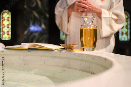 Valokuvatapetti Priest in front of a baptismal font with a bible