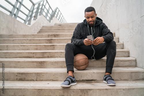 Athletic man using his mobile phone. Fototapet