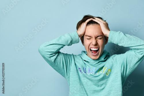 Fotografia, Obraz Half-length emotional portrait of a Caucasian teenage boy in a blue hoodie
