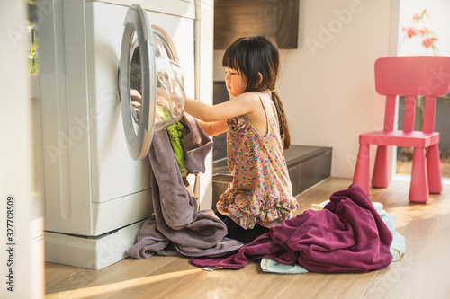 Tela child girl little helper in laundry room near washing machine and dirty clothes