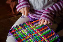 Child Weaving Potholder On Pla...