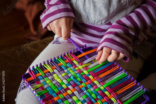 Photo Child weaving potholder on plastic loom