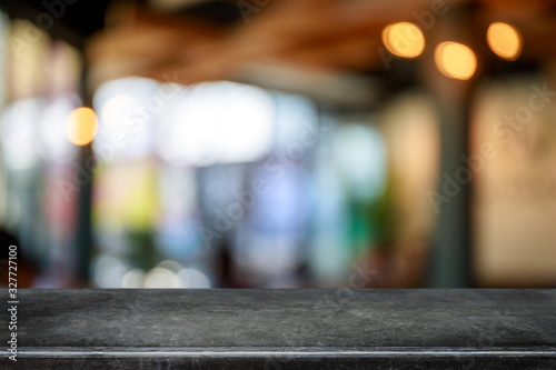 Fototapeta Empty black marble stone table top and blurred coffee shop and restaurant interior background - can used for display or montage your products. obraz