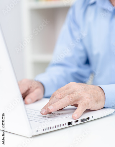 Close up hands of elderly person work on laptop computer in a office