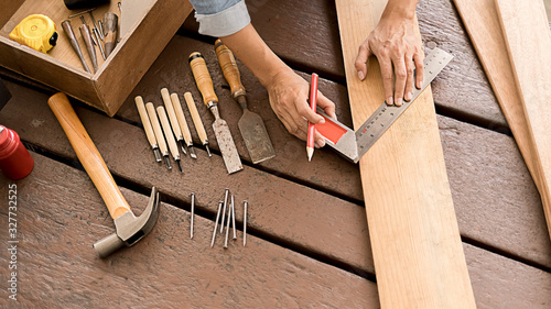 Carpenter working with equipment on wooden table in carpentry shop Fototapet