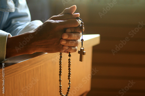 Fototapeta Senior man kneel, holding wooden rosary beads in hand with Jesus Christ holy cross crucifix in the church