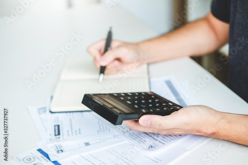 Fototapeta Man using calculator Accounting Calculating Cost Economic bills with money stack step growing growth saving money in home , finance concept obraz