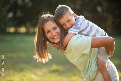 Photo Smiling cute kid enjoying piggyback ride outdoors