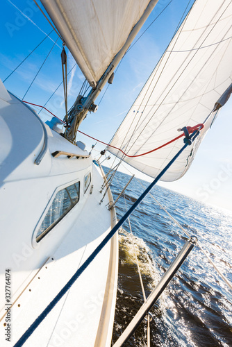 Fototapety, obrazy: White sloop rigged yacht sailing in an open Baltic sea on a clear sunny day. A view from the deck to the bow, mast and sails. Waves and water splashes. Estonia