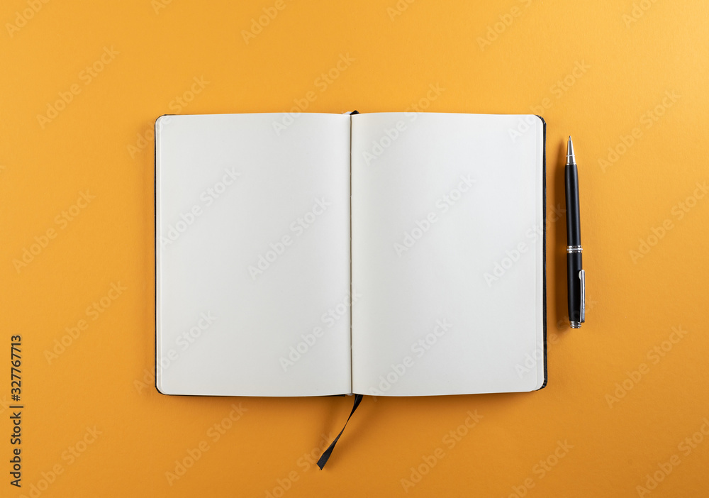 Fototapeta open diary or notebook with blank white pages on orange background template