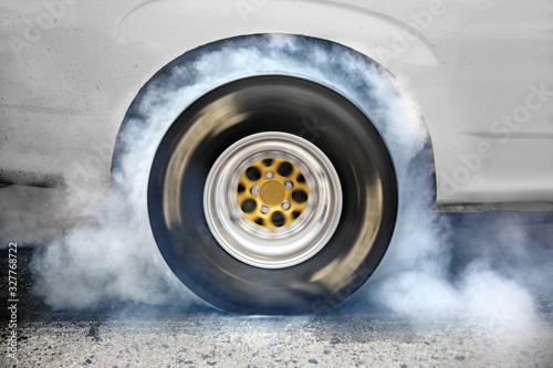 Vászonkép Drag racing car burns rubber off its tires in preparation for the race
