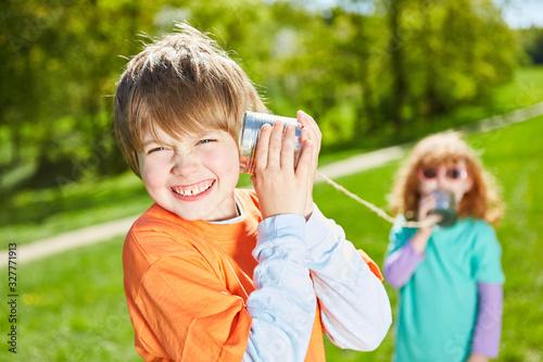 Photo Junge beim Telefonieren mit dem Dosentelefon