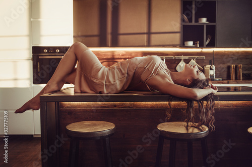 Cute sensual girl lies in underwear on a table in the kitchen. Canvas Print