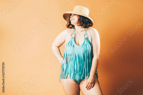 Fotomural Beautiful plus size model in blue swimsuit posing at the yellow background