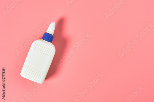 Bottle of glue lies on pink desk in workshop Wallpaper Mural