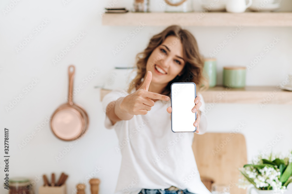 Phone blank screen. Phone with empty space for text in a female hand. The girl who holding a phone is  in defocus on the background - obrazy, fototapety, plakaty