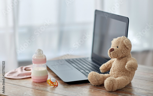 feeding and technology concept - bottle with baby milk formula, laptop computer, Tablou Canvas
