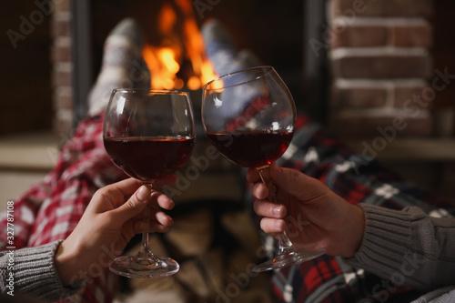 Obraz Couple with glasses of red wine near burning fireplace, closeup - fototapety do salonu