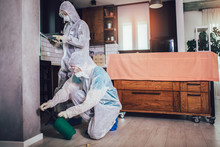 Specialists In Protective Suits Do Disinfection Or Pest Control In The Apartment.