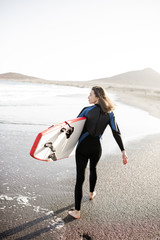Young woman in wetsuit walking with surfboard, leaving footprints on the sand behind, view from the backside. Water sport and active lifestyle concept