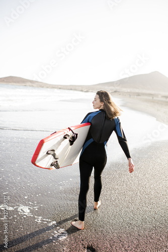 obraz PCV Young woman in wetsuit walking with surfboard, leaving footprints on the sand behind, view from the backside. Water sport and active lifestyle concept