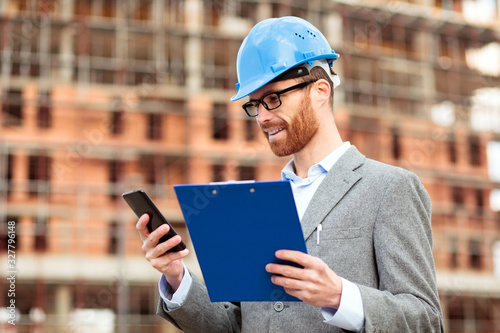 Fotografering Happy young caucasian architect or engineer inspecting construction site holding