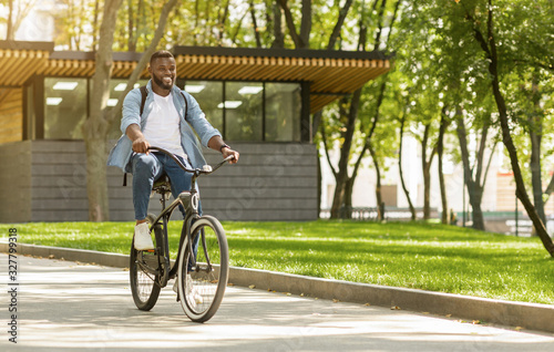 Fototapeta Eco Ride. Happy african american man riding bicycle in city obraz