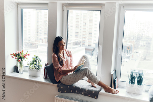 Attractive young woman in cozy pajamas reading a book while resting on the windo Canvas Print