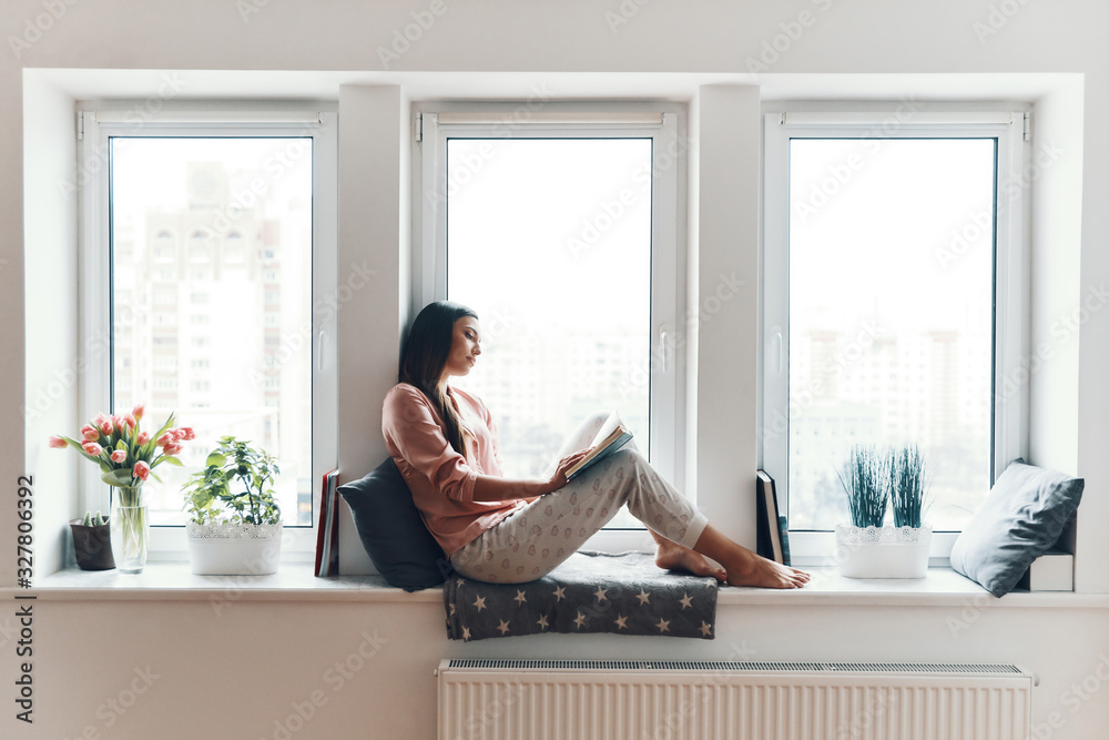 Fototapeta Carefree young woman in cozy pajamas reading a book while resting on the window sill at home