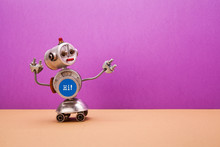 Four-wheeled Metallic Chat Bot Robot On Purple Brown Background. Silver Color Domestic Robotic Roller Assistant With Blue Interface Body. Creative Design Steampunk Toy, Copy Space